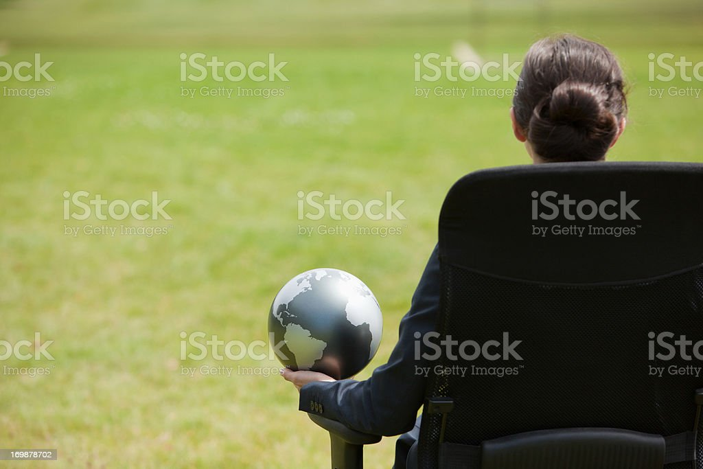 Businesswoman sitting outdoors holding globe stock photo