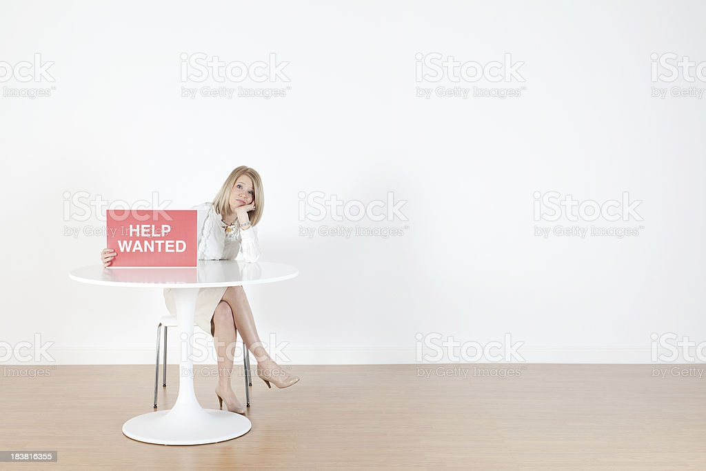 Businesswoman sitting with 'Help Wanted' sign royalty-free stock photo
