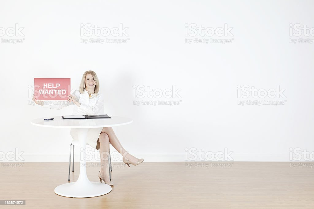 Businesswoman Sitting With Help Wanted Sign Royalty Free Stock Photo