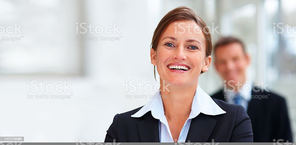 Businesswoman smiling with colleague in the background royalty-free stock photo