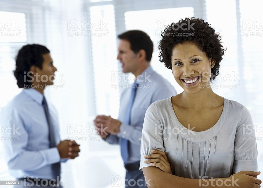 Businesswoman smiling with colleagues standing in the background royalty-free stock photo