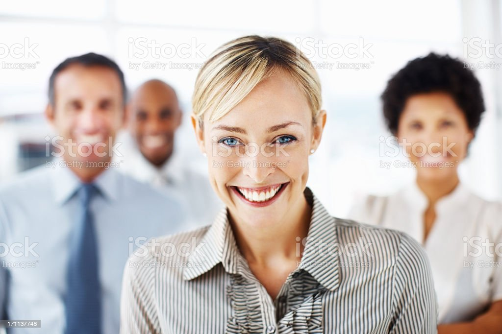 Businesswoman smiling with three colleagues behind her royalty-free stock photo