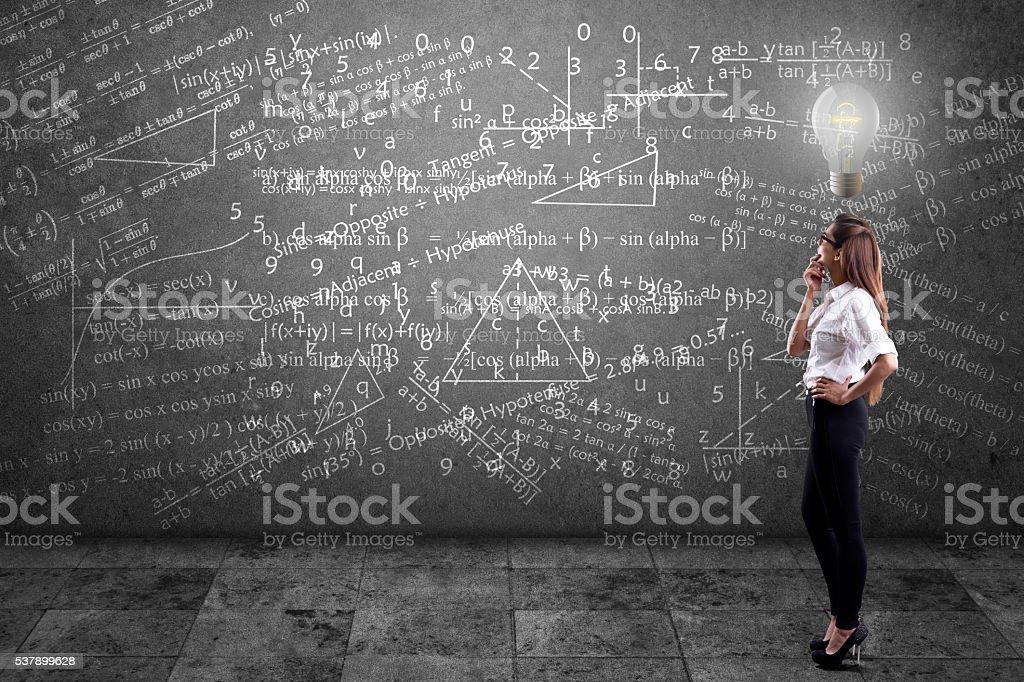 Businesswoman solving mathematical equation stock photo