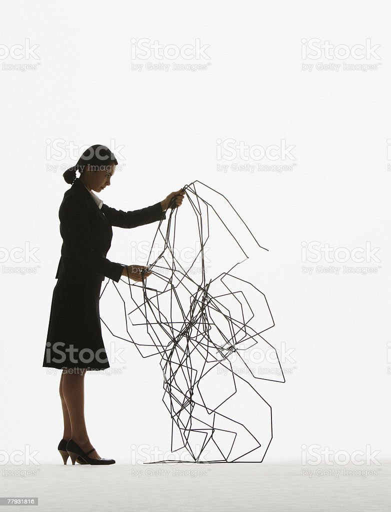 Businesswoman sorting through a pile of cable royalty-free stock photo