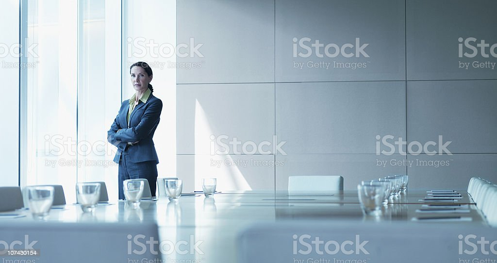 Businesswoman standing alone in conference room stock photo