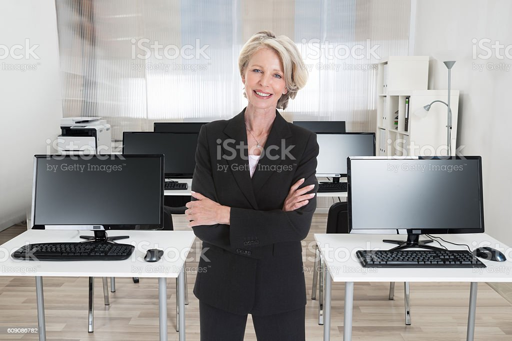 Businesswoman Standing Arms Crossed In Office stock photo