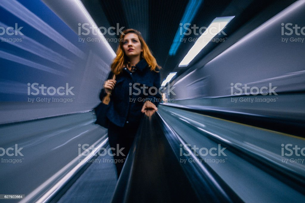 Businesswoman standing at escalator stock photo
