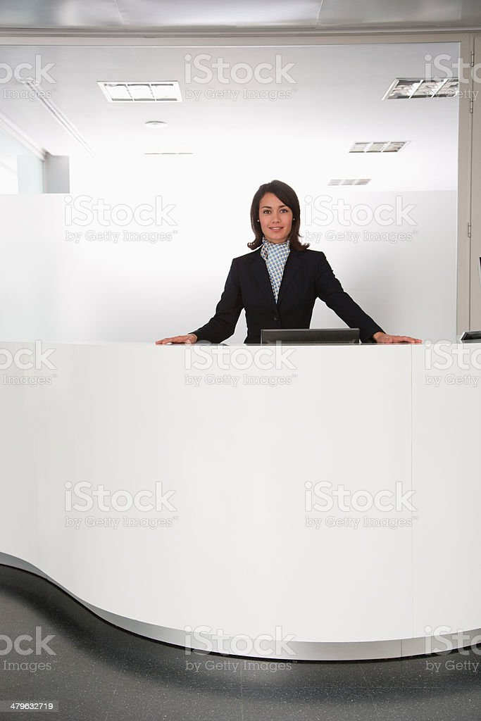 Businesswoman standing at reception desk stock photo