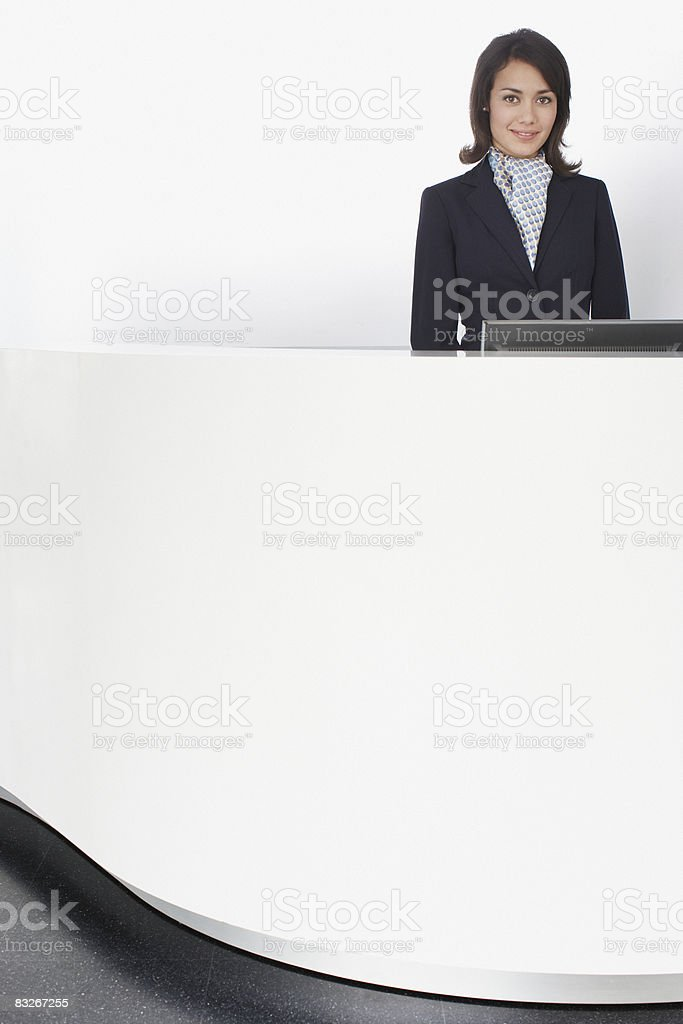 Businesswoman standing at reception desk royalty-free stock photo