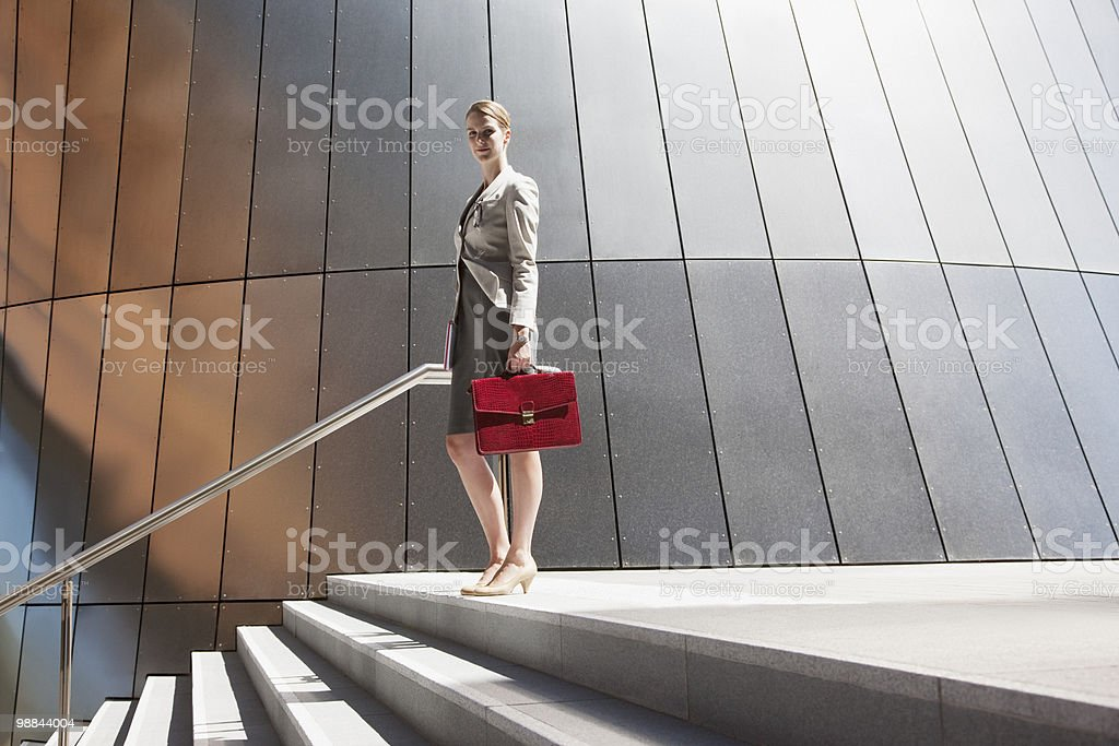 Businesswoman standing at top of steps outdoors stock photo