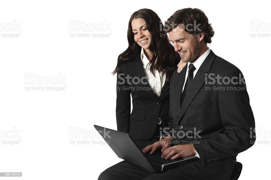 Businesswoman standing beside a businessman using laptop stock photo