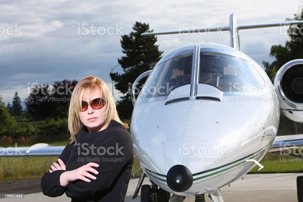Businesswoman standing by corporate jet royalty-free stock photo