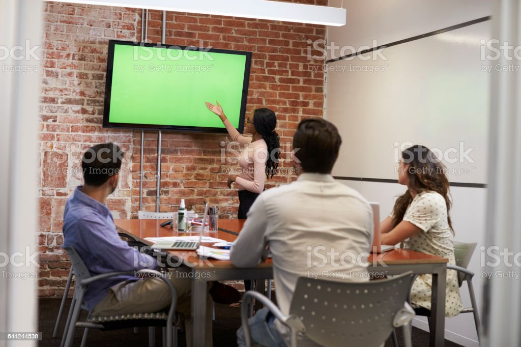 Businesswoman Standing By Screen To Deliver Presentation stock photo