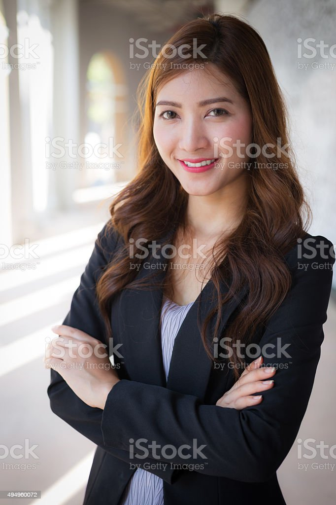 Businesswoman standing crossed arms with smiling face stock photo