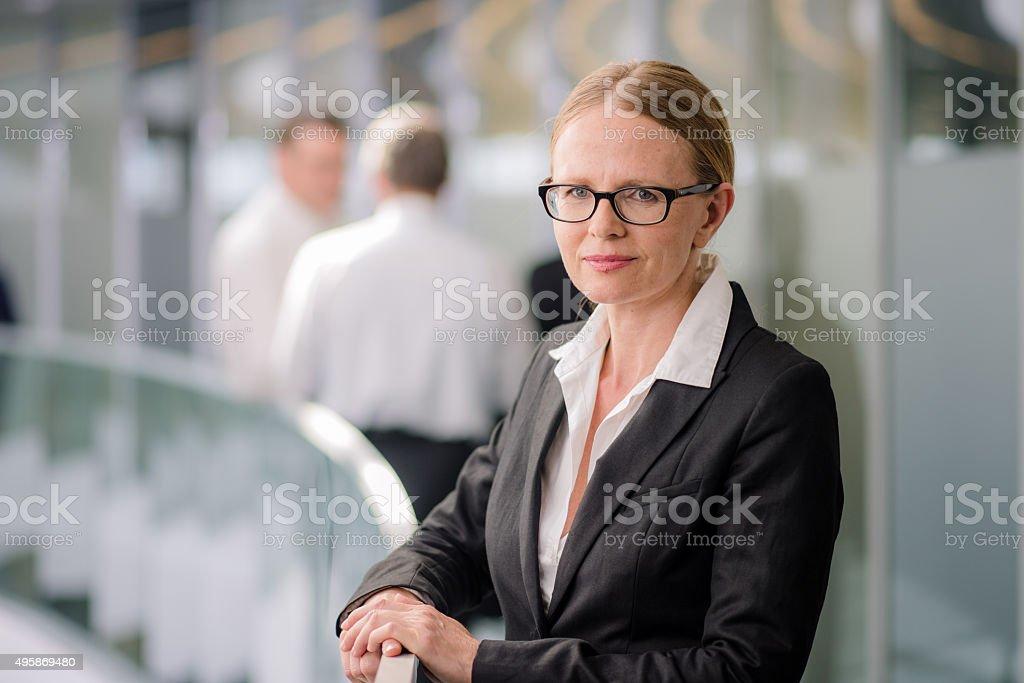 Businesswoman standing in corridor stock photo
