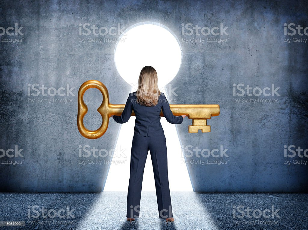 Businesswoman standing in front of keyhole holding a large key stock photo