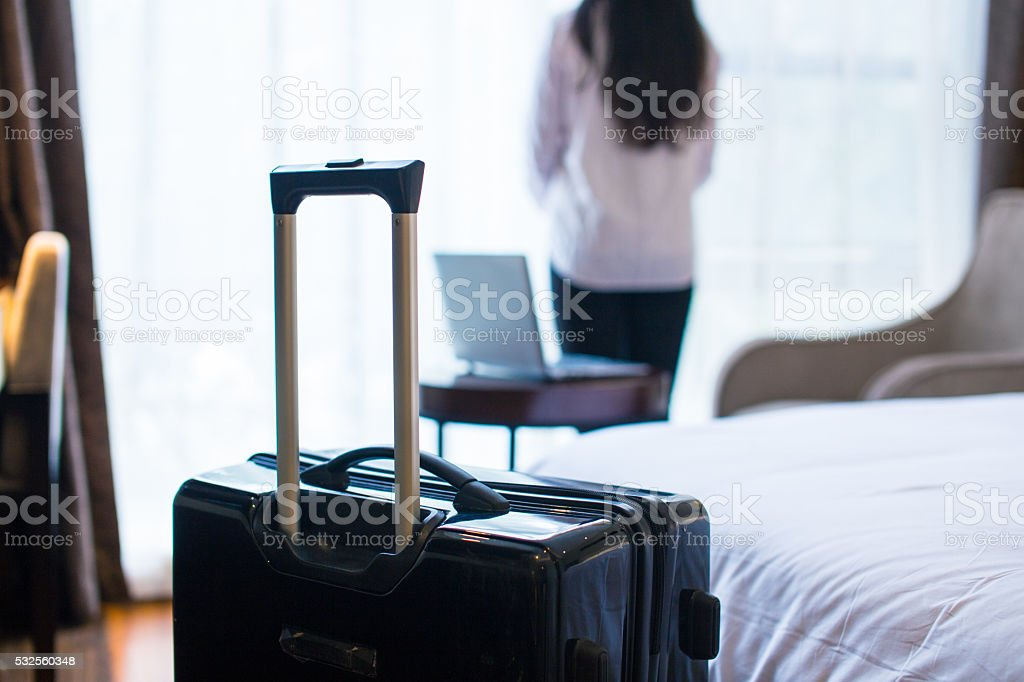 businesswoman standing in hotel room stock photo