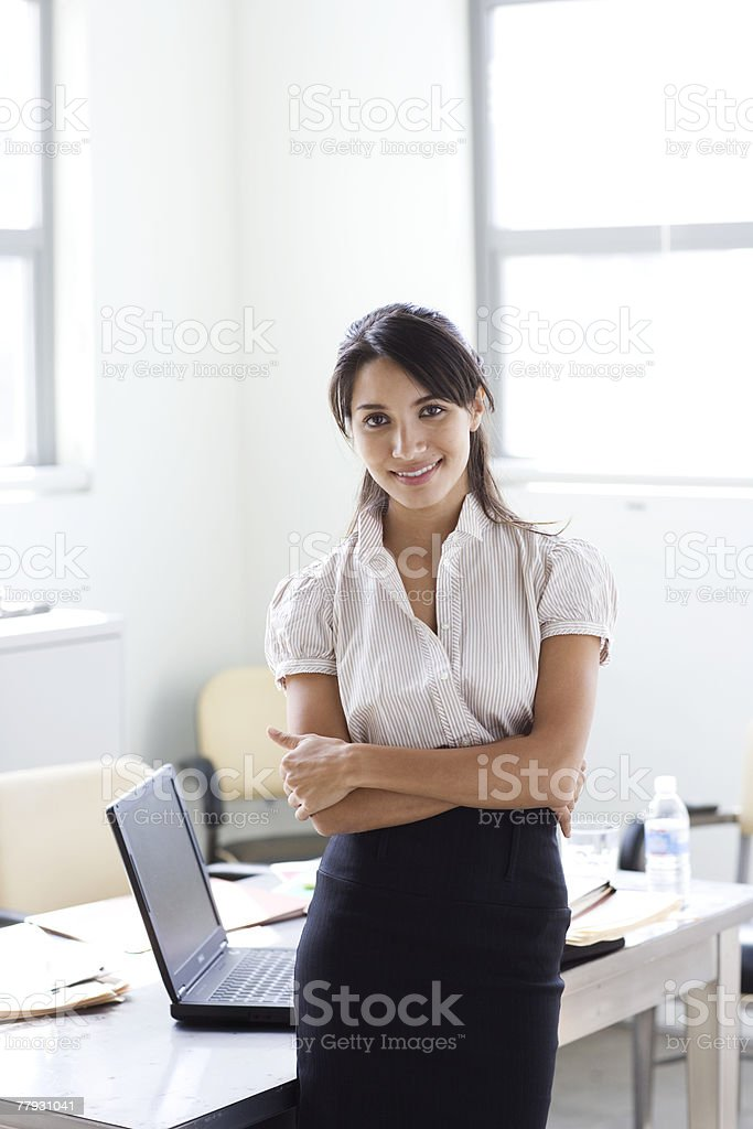 Businesswoman standing in office smiling royalty-free stock photo