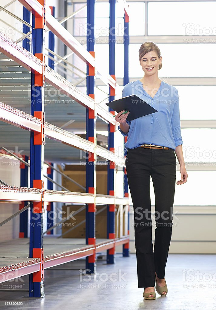 Businesswoman standing next to shelves in warehouse with clipboard royalty-free stock photo