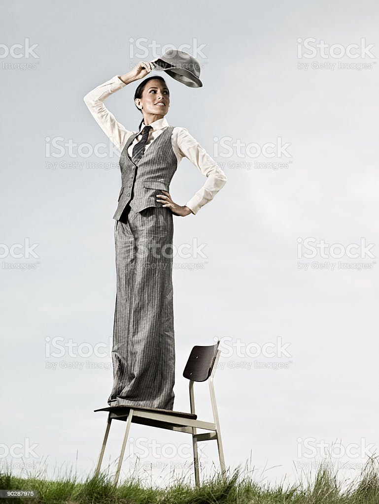 Businesswoman standing on chair outdoors royalty-free stock photo