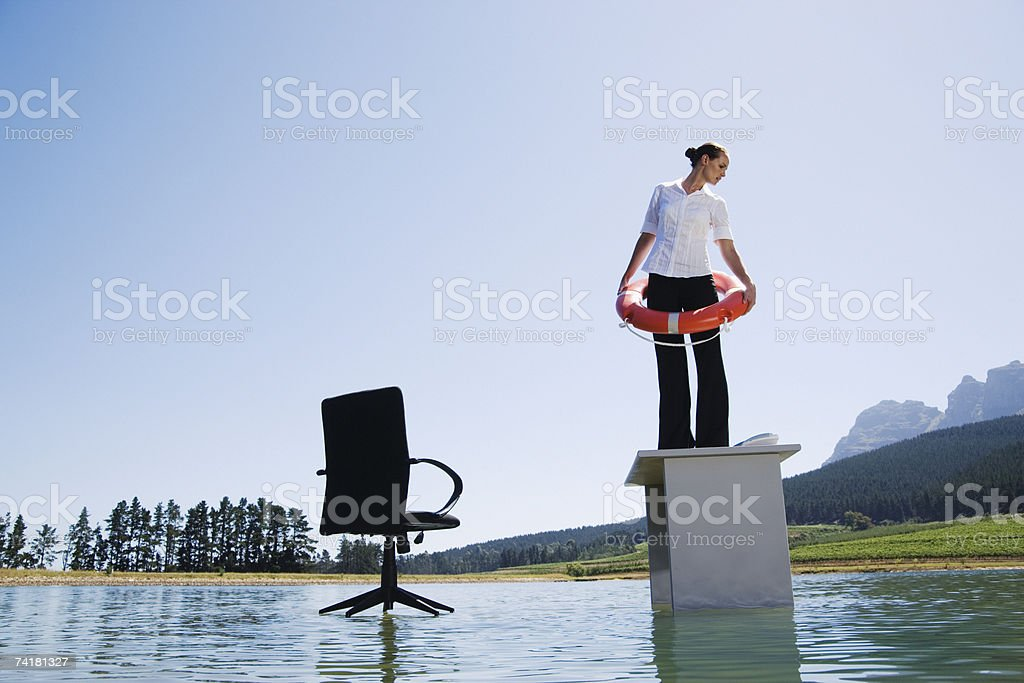Businesswoman standing on desk on water with flotation device royalty-free stock photo
