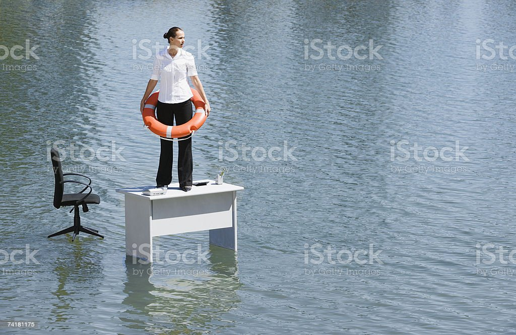 Businesswoman standing on desk with flotation device stock photo