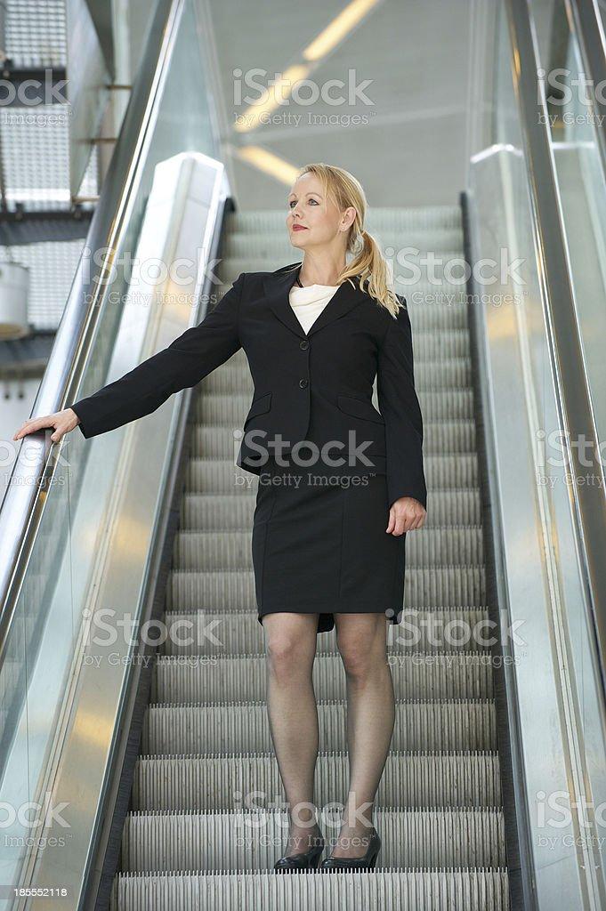 Businesswoman standing on escalator royalty-free stock photo