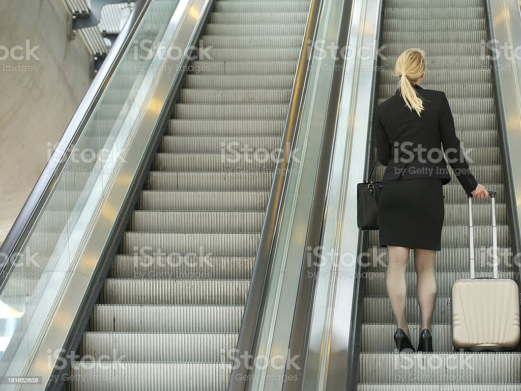 Businesswoman standing on escalator with travel bags royalty-free stock photo
