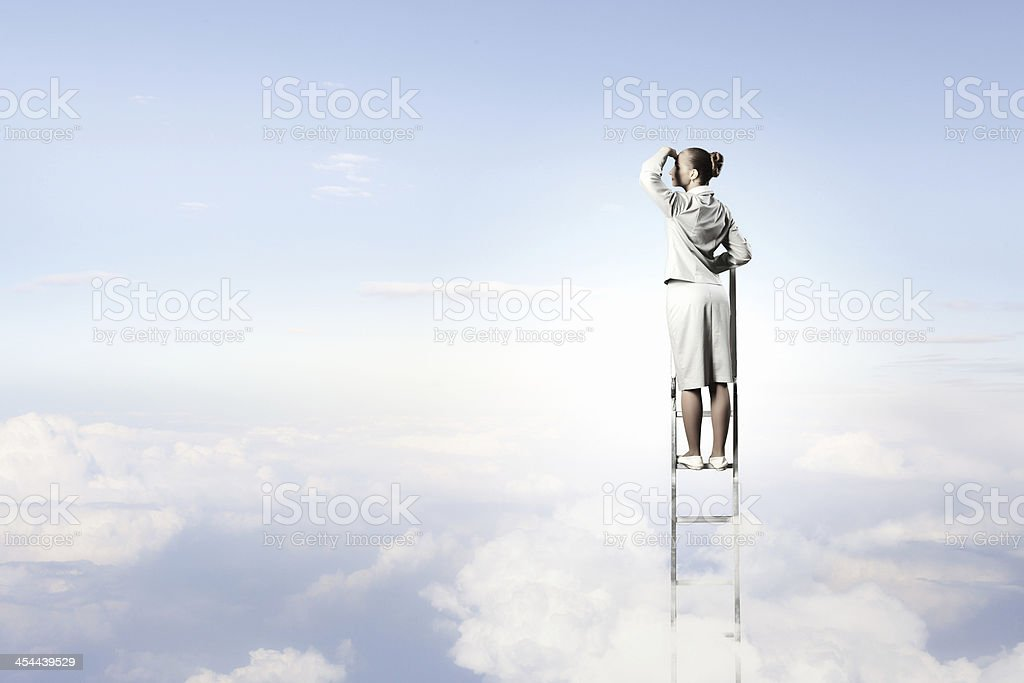 Businesswoman standing on ladder stock photo