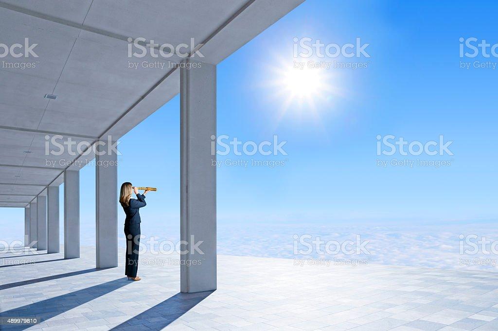 Businesswoman Standing On Pavilion Looking Through Spyglass stock photo