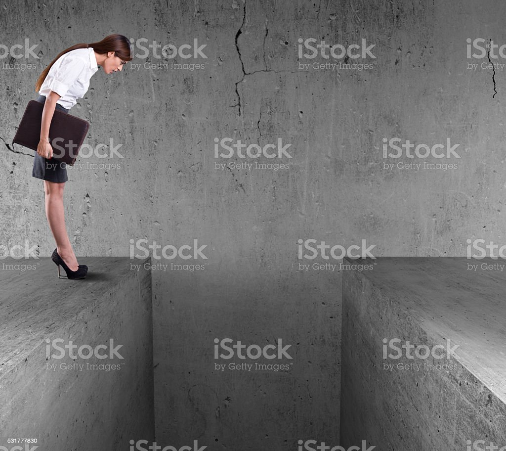 Businesswoman standing on the edge of wall and look down stock photo