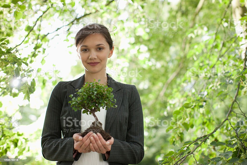 Businesswoman standing outdoors holding plant stock photo
