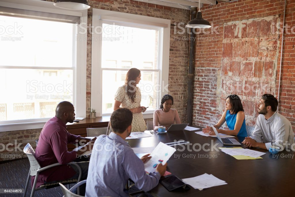 Businesswoman Standing To Address Boardroom Meeting stock photo