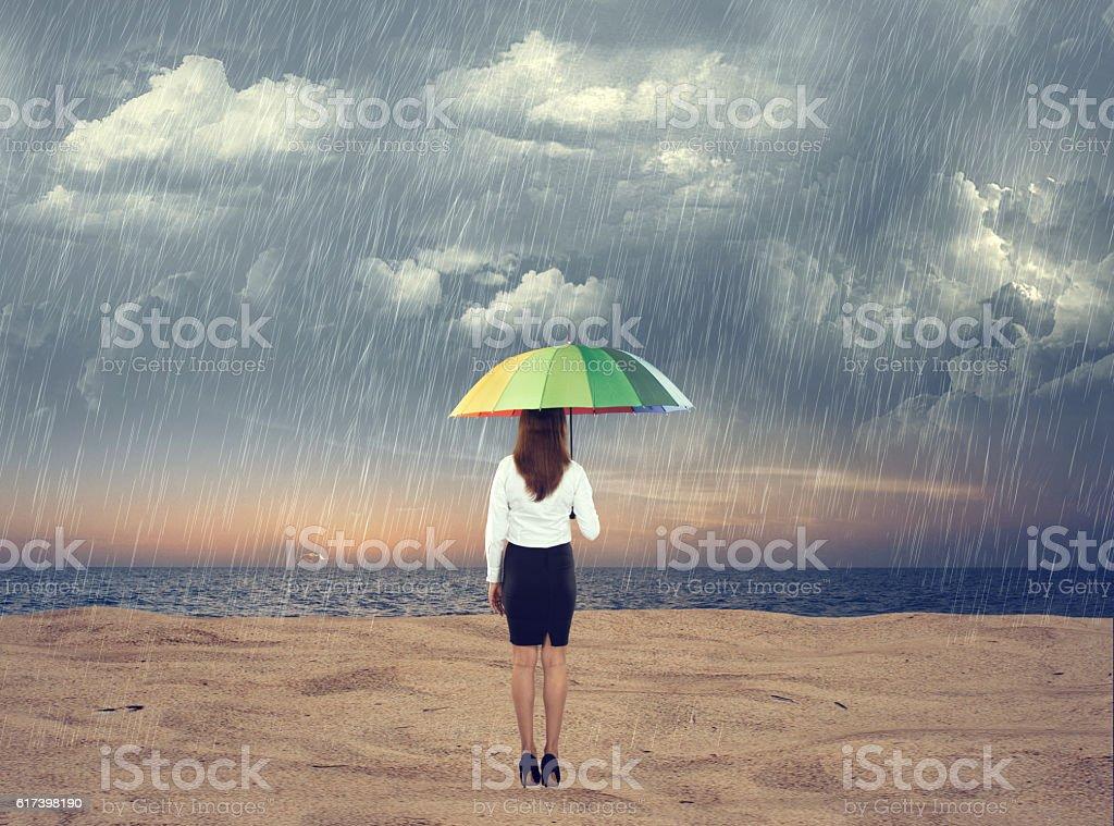 Businesswoman standing under an umbrella at beach stock photo