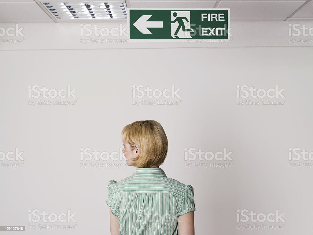 Businesswoman Standing Under Exit Sign stock photo