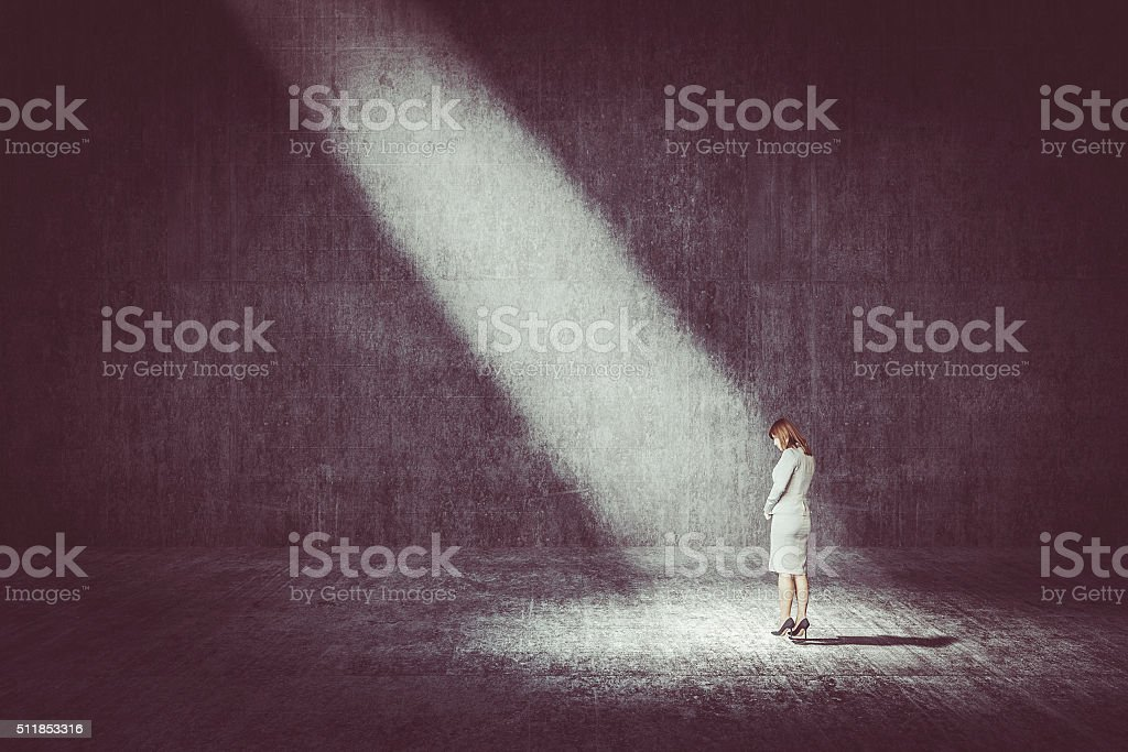 Businesswoman standing under the spotlight stock photo