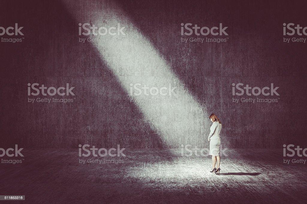Businesswoman standing under the spotlight stock photo