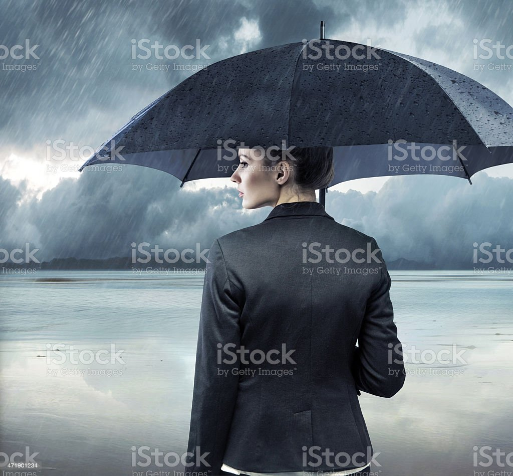 Businesswoman standing with an umbrella stock photo