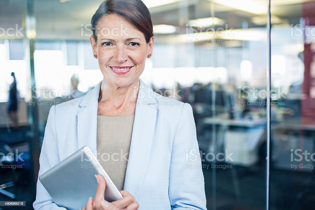 Businesswoman standing with digital tablet stock photo