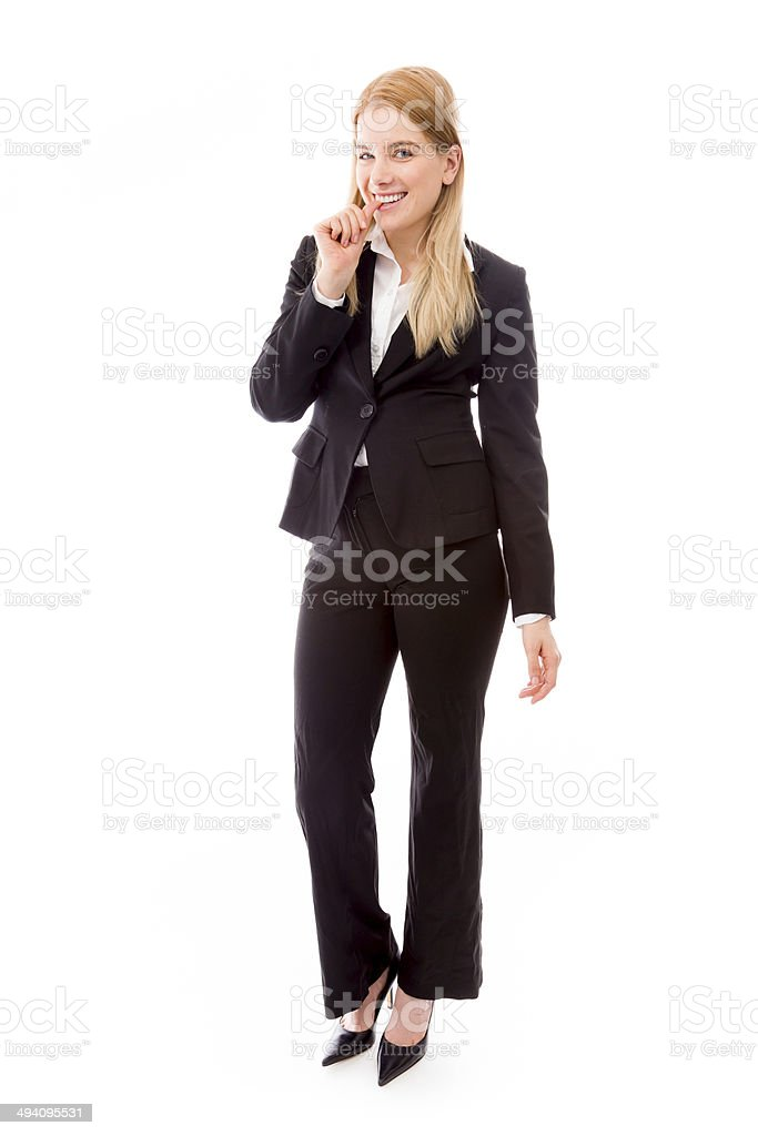 Businesswoman standing with finger in mouth stock photo