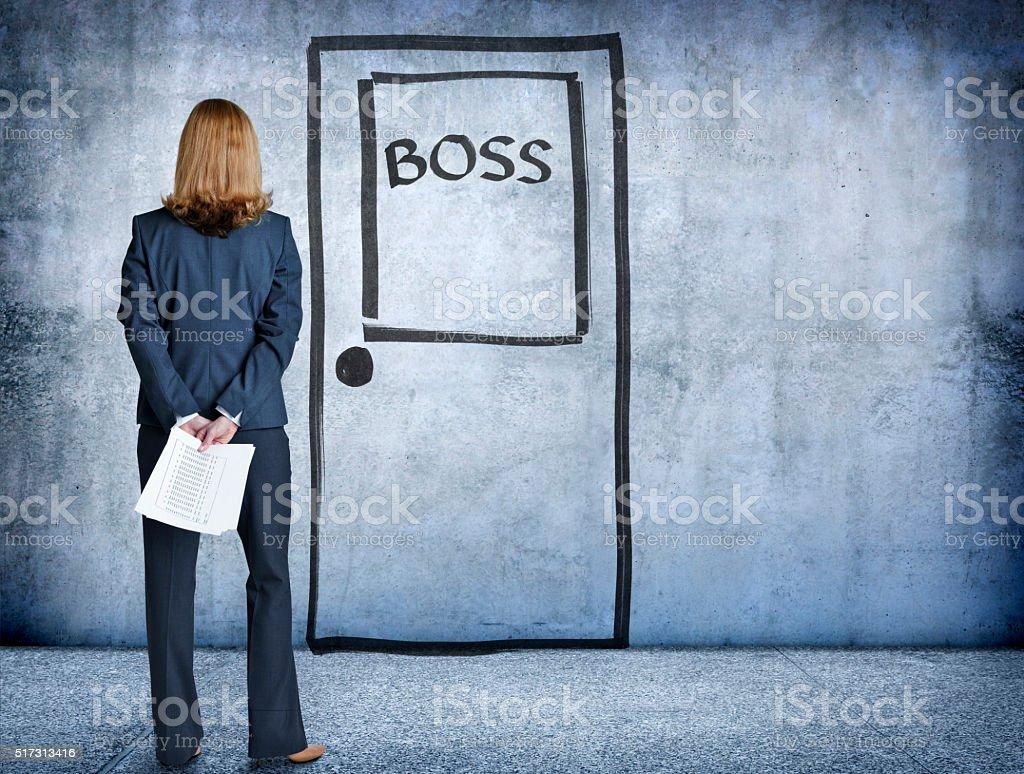 Businesswoman Standing With Report In Front Of Boss' Door stock photo