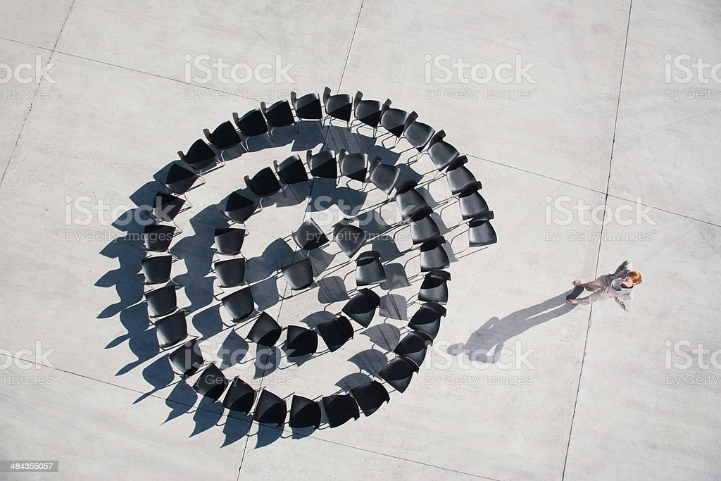 Businesswoman standing with spiral of office chairs stock photo