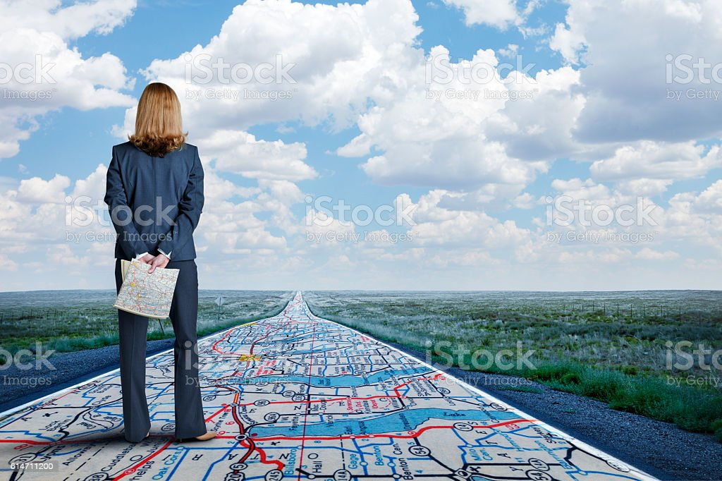 Businesswoman Stands On Long Road With Road Map Painted On It stock photo