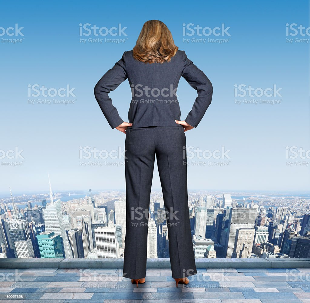 Businesswoman Stands On The Edge Of Building Looking Down stock photo