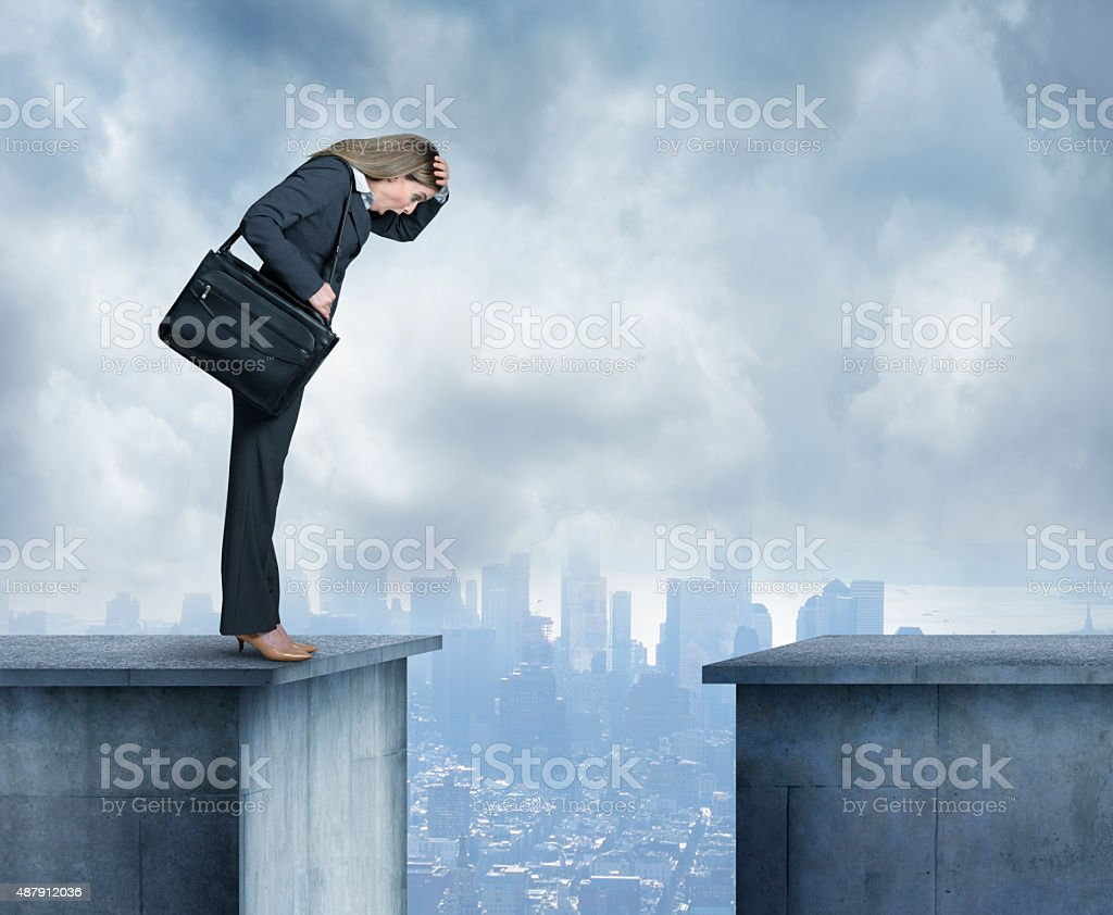Businesswoman stares at space between two buildings stock photo