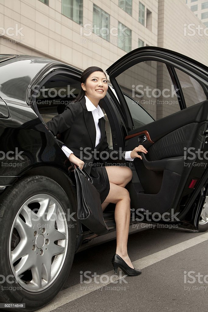 Businesswoman stepping out a car stock photo