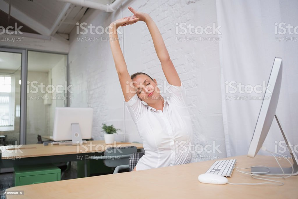 Businesswoman stretching hands in office stock photo