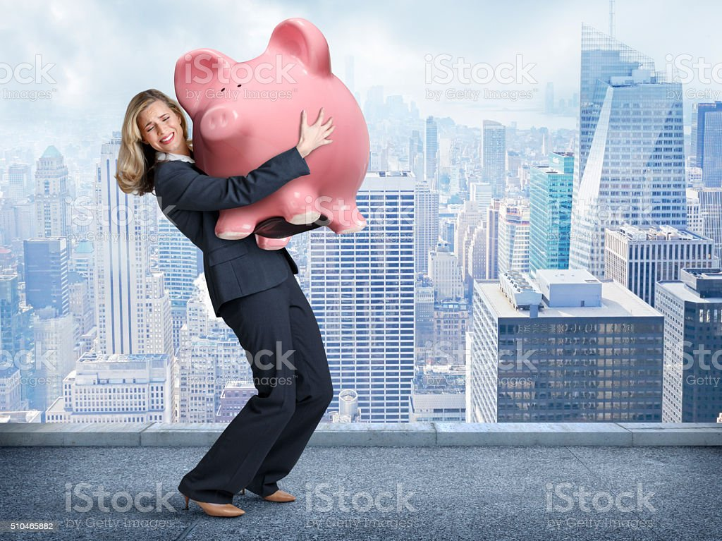 Businesswoman Struggling To Carry A Large Pink Piggy Bank stock photo