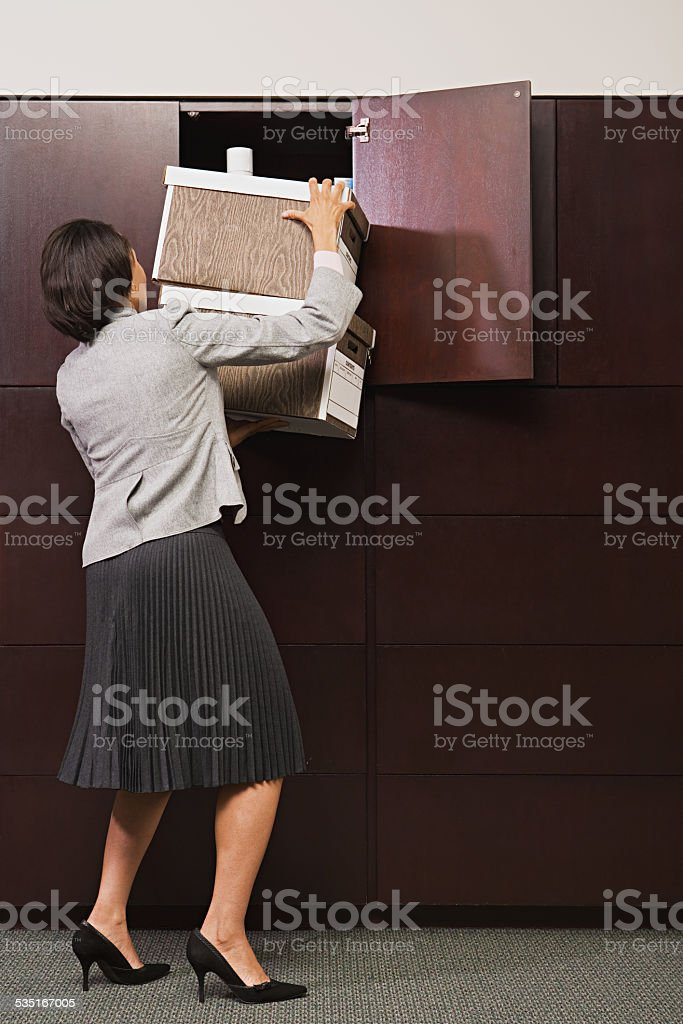 Businesswoman struggling with files stock photo