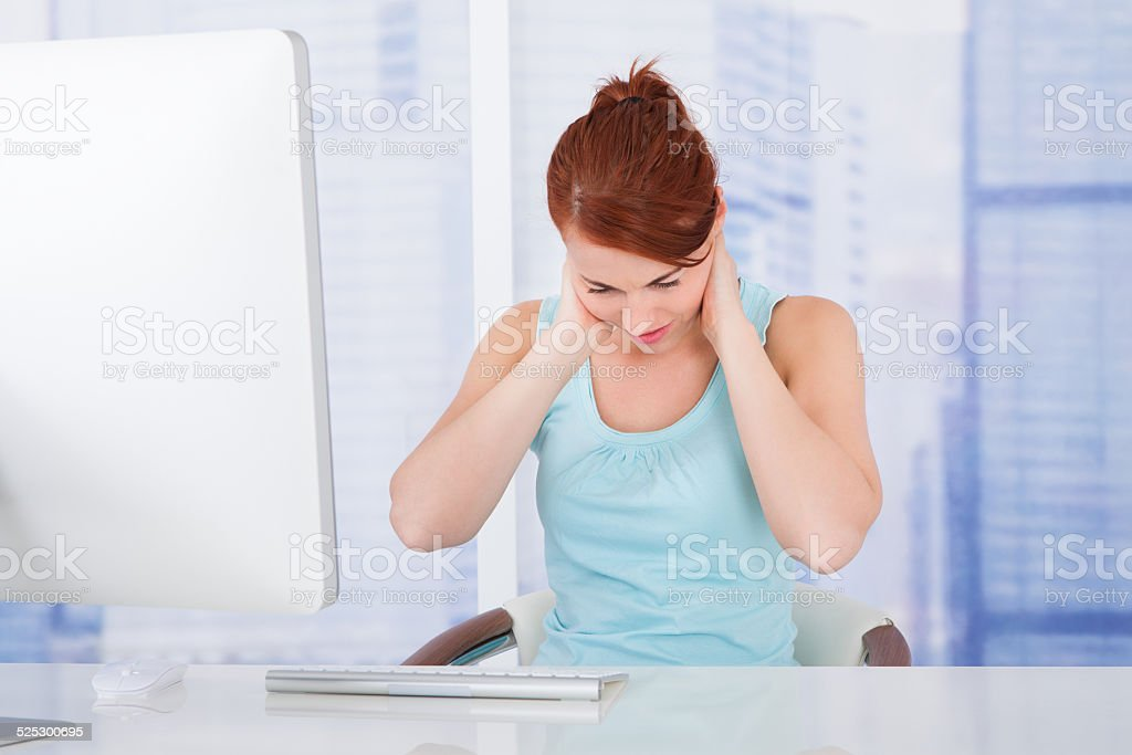 Businesswoman Suffering From Neckache At Computer Desk stock photo